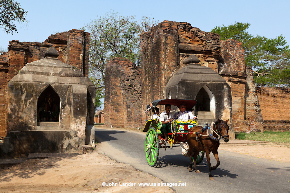 Tharabar Gate Horse Cart, Old Bagan - The gateway to Old Bagan is Tharabar Gate, the best preserved remains of the wall surrounding the former original palace site built in the 9th century. The gateway has two niches which house Burmese nat, who guard the gate and are treated with deep respect by the locals. Shown is Lady Golden Face.