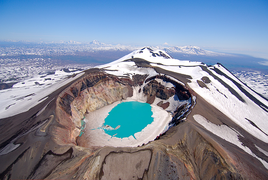 The azure blue waters filling the crater of Maly Semyachik Volcano are rimmed with ice in June/n Kamchatka; water; Russia; Maly Semyachik Volcano; crater