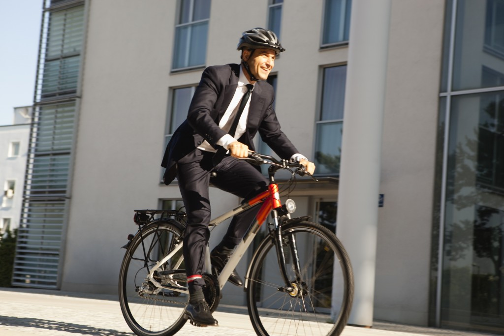 Blurred motion of mature businessman riding bicycle