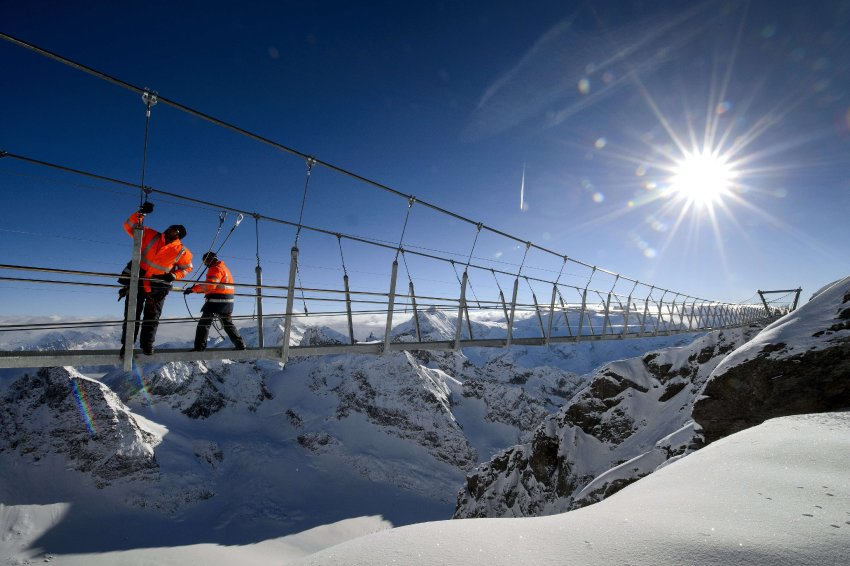 Construction workers check cables on the highest suspension bridge in Europe on December 1, 2012 in the Titlis mountain above Engelberg, Central Switzerland. To mark the 100th anniversary of the Titlis cableways, a 100-meter-long suspension bridge is being build at more than 3041 meters above sea level and will be the highest suspension bridge in Europe. The bridge is expected to be opened on December 7, 2012. AFP PHOTO / FABRICE COFFRINI